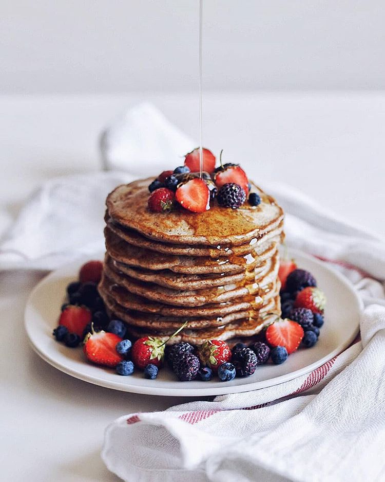 A stack of golden buckwheat pancakes by @allosimone being drizzled in maple syrup and surrounded by berries